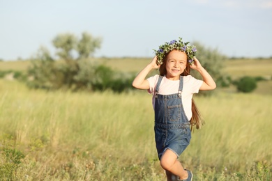 Cute little girl wearing flower wreath outdoors, space for text. Child spending time in nature