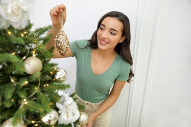 Young woman decorating Christmas tree at home