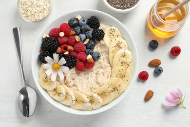 Tasty oatmeal porridge with berries, banana and chia seeds served on light wooden table, flat lay