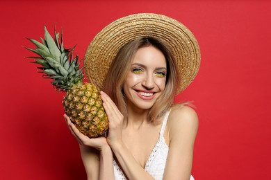 Young woman with fresh pineapple on red background. Exotic fruit