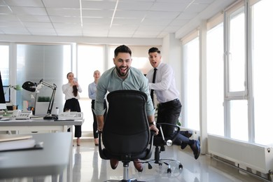 Happy office employees riding chairs at workplace
