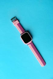 Trendy smart watch for kids on light blue background, top view