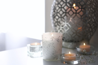 Beautiful burning candles on table at home. Space for text