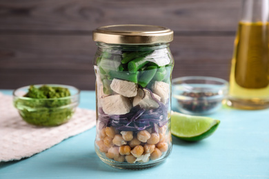 Glass jar with healthy meal on light blue wooden table