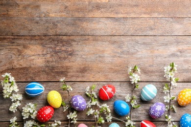 Flat lay composition with painted Easter eggs and blossoming branches on wooden background. Space for text