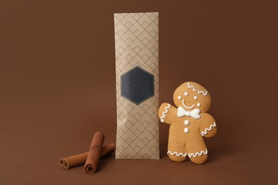 Scented sachet, cinnamon and gingerbread man on brown background