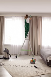 Professional janitor on ladder near window with curtains in bedroom. Cleaning service