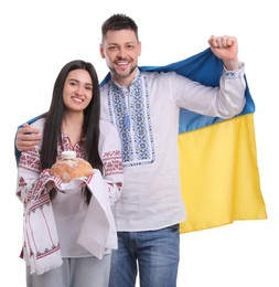 Happy couple with flag of Ukraine and traditional korovai on white background