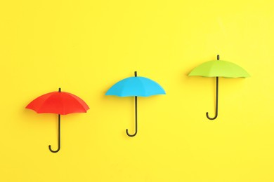 Bright toy umbrellas on yellow background, flat lay