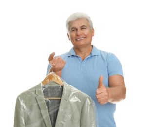 Senior man holding hanger with jacket in plastic bag on white background. Dry-cleaning service