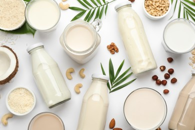 Different vegan milks and ingredients on white background, flat lay