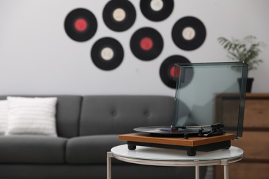 Stylish turntable with vinyl disc in living room