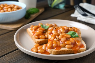 Toasts with delicious canned beans on wooden table, closeup