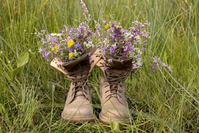 Boots with beautiful wild flowers on grass