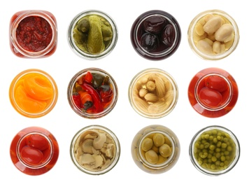 Set of jars with pickled foods on white background, top view
