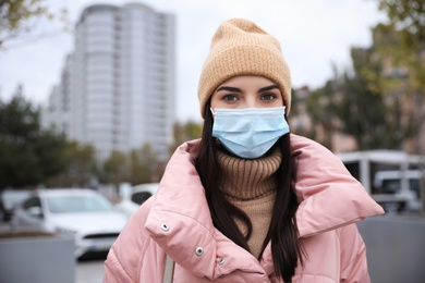 Young woman in medical face mask walking outdoors. Personal protection during COVID-19 pandemic
