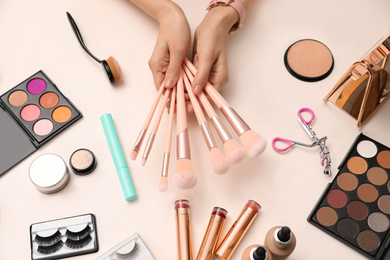 Beauty blogger with set of make up brushes at table, top view