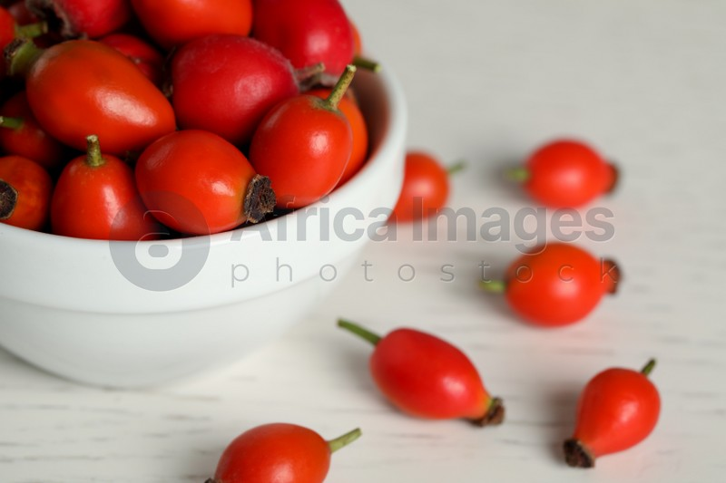 Ripe rose hip berries with bowl on white wooden table, closeup. Space for text