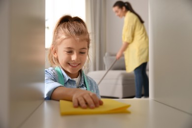 Little girl helping her mother with cleaning living room