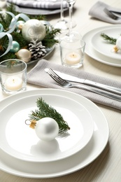 Festive table setting with beautiful dishware and Christmas decor on white wooden background