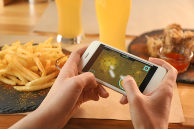 Woman playing game using smartphone at table with tasty snacks, closeup