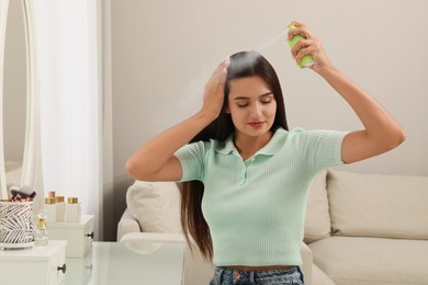 Woman applying dry shampoo onto her hair at home