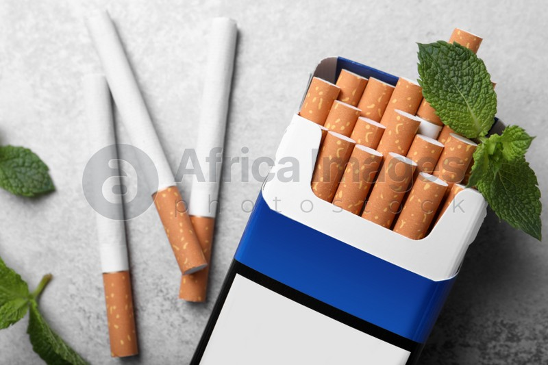 Pack of menthol cigarettes and mint leaves on grey table, flat lay