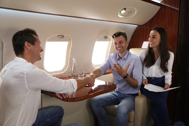Young people discussing business contract during flight