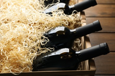 Crates with bottles of wine on wooden background, closeup