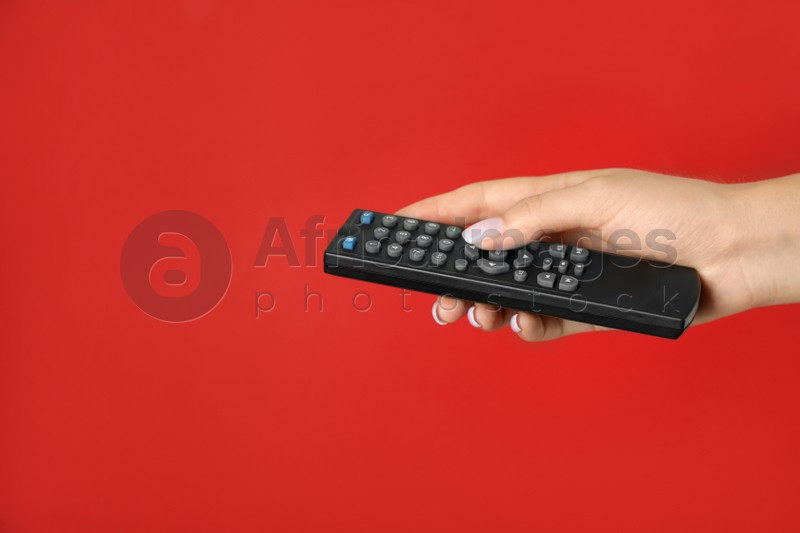 Woman holding remote control on red background, closeup