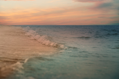 Ocean waves rolling on sandy beach under sky with clouds at sunset, closeup