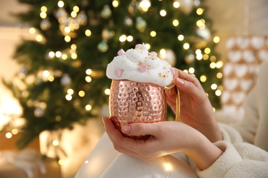 Woman holding cup of delicious drink with whipped cream and marshmallows near Christmas tree indoors, closeup