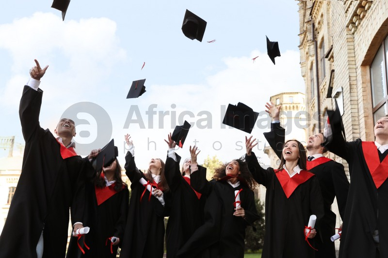 Happy students with diplomas throwing graduation hats in air outdoors