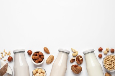 Vegan milk and different nuts on white background, flat lay. Space for text