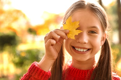 Happy girl with yellow leaf in sunny park. Autumn walk