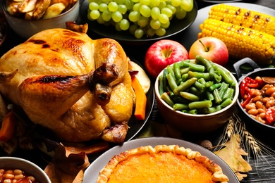 Traditional Thanksgiving day feast with delicious cooked turkey and other seasonal dishes served on black wooden table, closeup