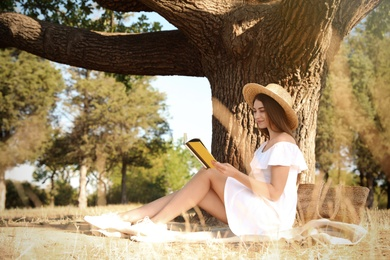 Young woman reading book near tree in park