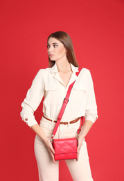 Beautiful young woman in casual outfit with stylish bag on red background