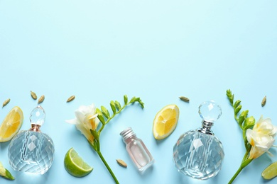 Flat lay composition with elegant perfumes on light blue background, space for text