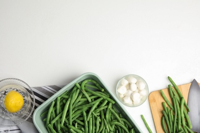 Flat lay composition with raw green beans on white table. Space for text