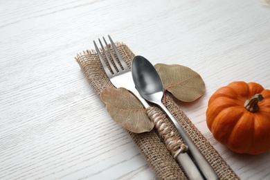 Cutlery with leaves and pumpkin on white wooden background, closeup. Table setting elements