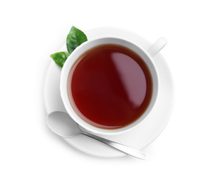 Cup of aromatic black tea, spoon and green leaves on white background, top view