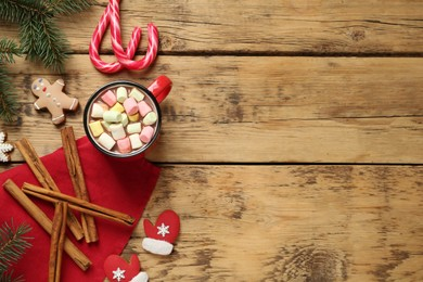 Delicious hot chocolate with marshmallows and gingerbread cookies on wooden table, flat lay. Space for text
