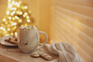 Tasty hot drink with marshmallows against Christmas lights. Space for text
