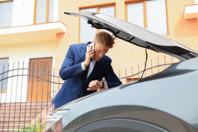 troubled young businessman talking on phone near broken car outdoors