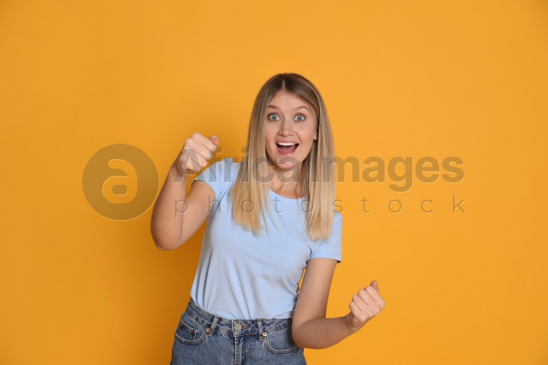 Emotional young woman pretending to drive car on yellow background