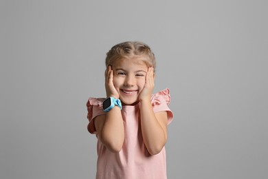 Little girl with smart watch on grey background