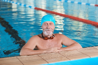 Sportive senior man in indoor swimming pool