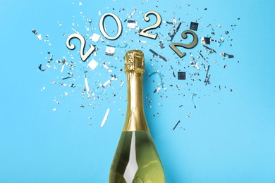Bottle of sparkling wine, shiny confetti and number 2022 on light blue background, flat lay. Happy New Year
