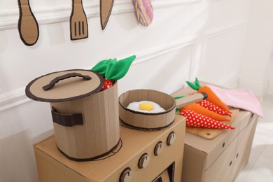 Toy cardboard kitchen with stove and utensils indoors